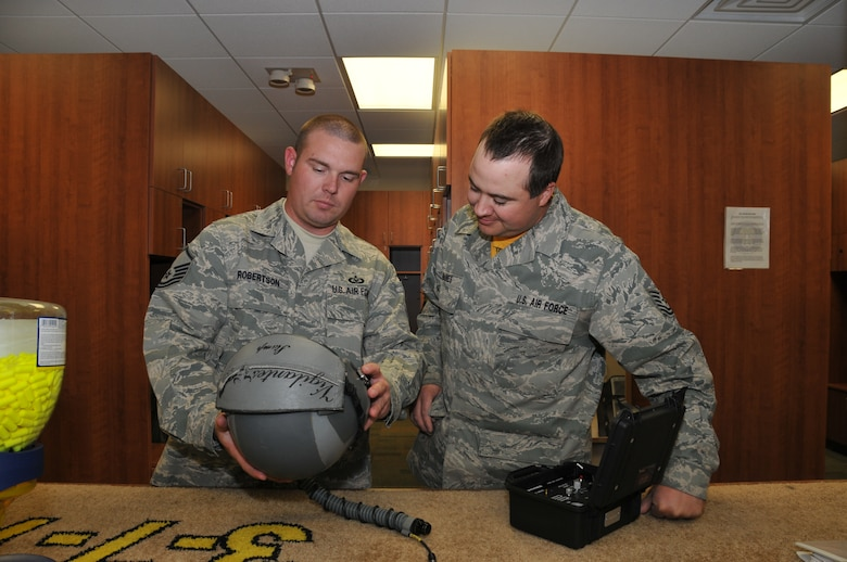 120th Fighter Wing Master Sgt. Raegen Robertson and Tech. Sgt. James Raines inspect a helmet during a post-flight check in the Aircrew Flight Equipment section on June 24, 2011.  (U.S. Air Force photo by Senior Master Sgt. Eric Peterson.)