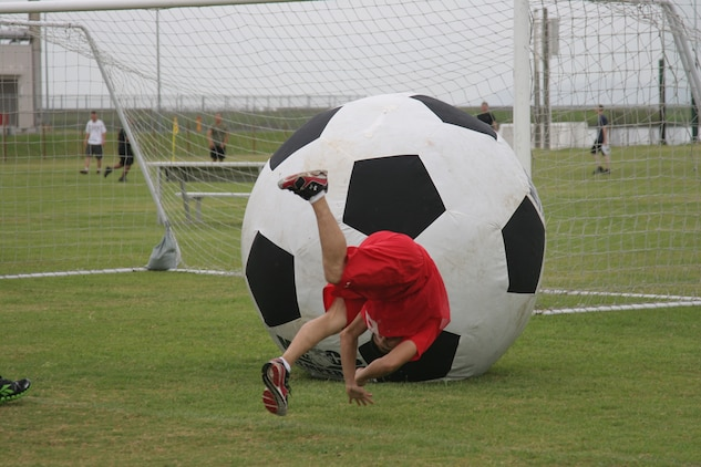 Cpl. Delshan R. Martinez, a Combat Logistics Company 36 motor vehicle operator, trips over himself as he scores a goal against Marine Aviation Logistics Squadron 12 during an earth ball game at Penny Lake field here Sept. 16. CLC-36 won a best-of-three series with a combined score of 2-0.