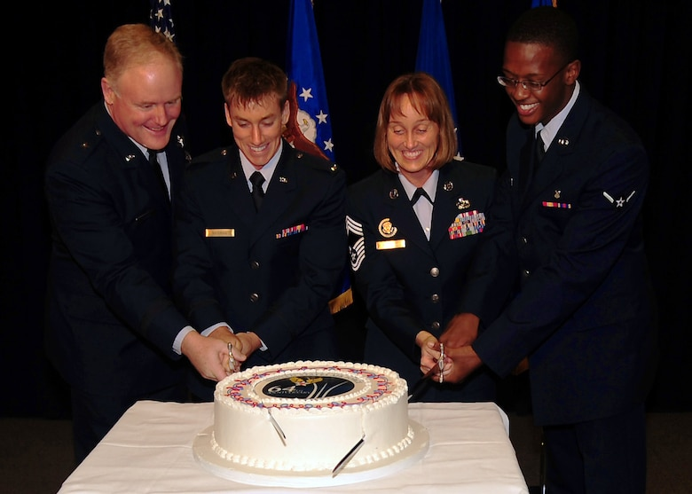Brig. Gen. Roger Teague, SMC vice commander, and Chief Master Sgt. Vicki Robinson are joined by Los Angeles AFB's youngest officer and enlisted members for the ceremonial cake cutting marking the Air Force's 64th birthday, Sept. 16. (Photo by Jim Gordon)