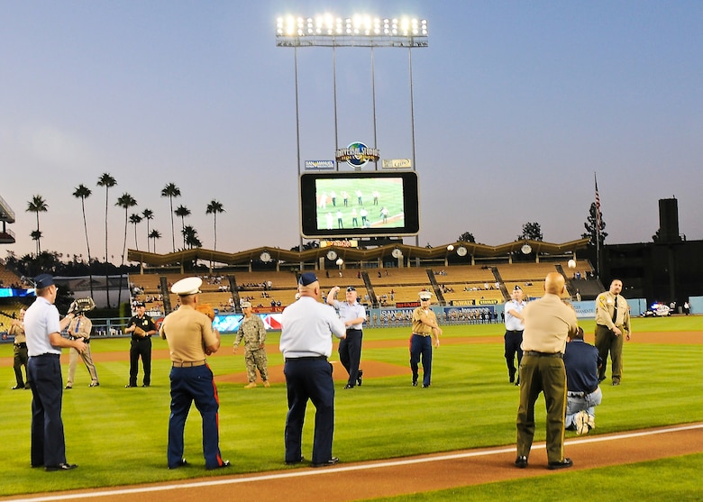 Brig. Gen. Roger Teague, SMC vice commander and Col Frank Simcox, 61st ABG commander, join representatives from other armed forces, and local police and fire departments in a mass first pitch and catch prior to the Los Angeles Dodgers game, Sept. 12. The Dodgers recognized the military and first responders at the game in observance of the 10th Anniversary of the 9-11 terrorist attacks. (Photo by Joe Juarez)