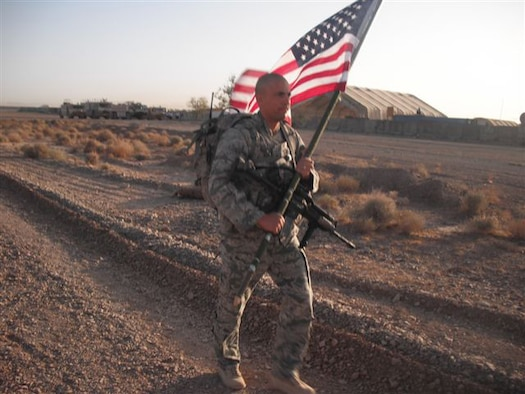 U.S. Air Force Security Forces 2nd Lt. Jason Sawyers, 838th Air Expeditionary Advisory Group, marches with the American Flag at Shindand Air Base, Shindand, Afghanistan September 11, 2011. Airmen from the 838th AEAG participated in a 24-hour ruck march in honor of the victims of the September 11, 2001 attacks.  (U.S. Air Force photo by Master Sgt. Jason Brown)