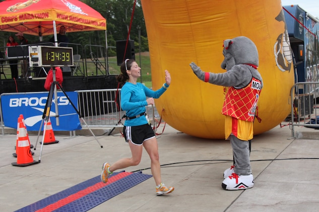 A runner crossing the finish line is greeted with a high-five from Molly, one of the Marine Corps Marathon mascots, Sept. 17.  The goal of the MCM is to promote physical fitness, community goodwill and showcase the organizational skills of the Corps.
