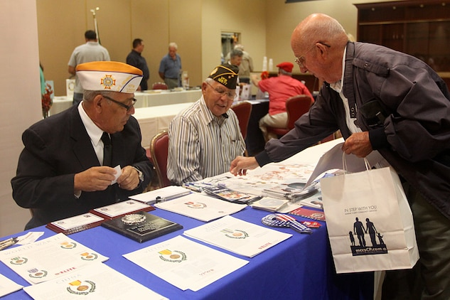 Robert Reid (right), a retired staff sergeant, reaches for a brochure during Camp Pendleton's 18th Annual Military Retiree Expo at the base's South Mesa Club, Sept. 17. The expo, which was sponsored by Marine Corps Community Services, featured various vendors who offered information to the retirees and their family members to help them throughout the course of their retirement.