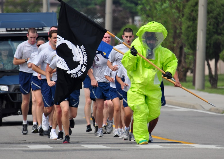 Senior Airman Destry Swadowski, 51st Civil Engineer Squadron with the emergency management flight, carries the POW/MIA flag in his HAZMAT suit Sept. 16, 2011 during the POW/MIA 24-hour run. The POW/MIA flag was carried non-stop by runners around a 1.2-mile course to honor all those who are POW/MIA and to remember those who are still missing today. Members of the Osan's Air Force Sergeants Association honored all POW/MIAs during several ceremonies and events Sept. 12-16. (U.S. Air Force photo/Tech. Sgt. Chad Thompson)