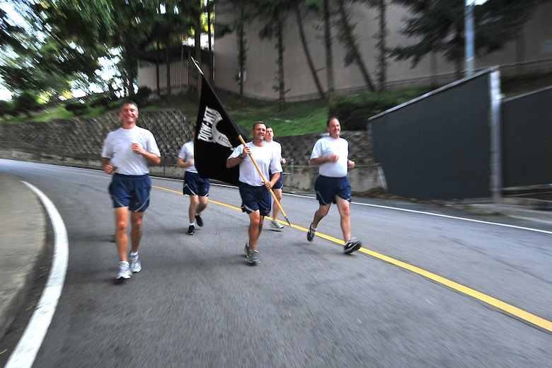 Col. Patrick McKenzie, Chief Master Sgt. Deno Mackin and Col. Mark DeLong, 51st Fighter Wing leadership, carry the POW/MIA flag for the first leg of the POW/MIA 24-hour run Sept. 15, 2011. The POW/MIA flag was carried non-stop by runners around a 1.2-mile course to honor all those who are POW/MIA and to remember those who are still missing today. Members of the Osan's Air Force Sergeants Association honored all POW/MIAs during several ceremonies and events Sept. 12-16. (U.S. Air Force photo/Senior Airman Adam Grant)