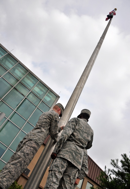 Airmen with the base honor guard raise the American flag and the POW/MIA flag Sept. 12 at the base flagpole. About 100 Airmen formed up at the 51st Fighter Wing headquarters building for the ceremony to formally start a week honoring all the prisoners of war and those still missing in action. Members of the Osan's Air Force Sergeants Association honored all POW/MIAs during several ceremonies and events Sept. 12-16. (U.S. Air Force photo/Tech. Sgt. Chad Thompson)
