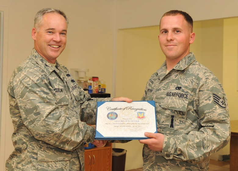 MOUNTAIN HOME AIR FORCE BASE, Idaho – Staff Sgt. Brian Vetter, 366th Maintenance Operations Squadron standardization lead crew 3 member, receives an award from Col. James McClellan, 366th Maintenance Group commander, here Sept. 7. Vetter received  Air Combat Command's Outstanding Armament Systems Technician Award for identifying a munitions fuse flaw.(U.S. Air Force photo by Airman 1st Class Heather Hayward)
