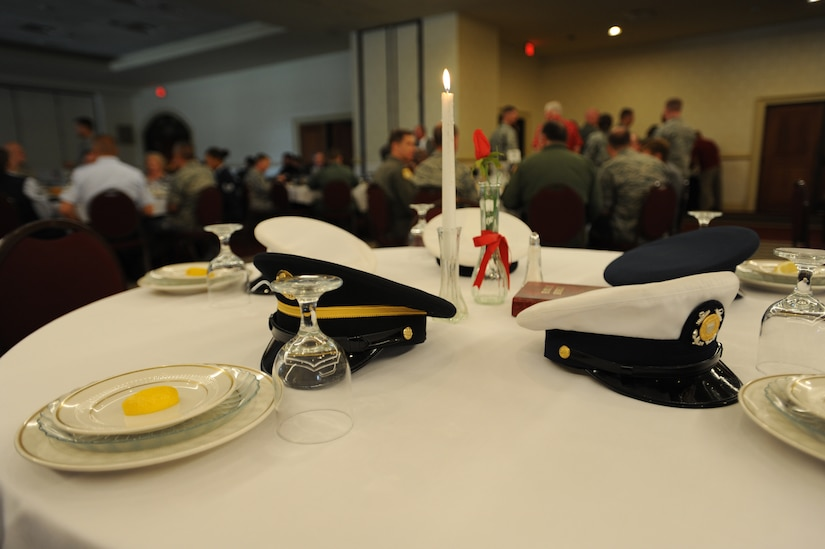 United States Navy, Air Force, Army, Marine Corps, and Coast Guard service hats rest on a Prisoner of War/Missing in Action table as part of a presentation during a POW/MIA luncheon Sept. 16 on Joint Base Charleston. The setting of the POW/MIA table is a time-honored ceremony in recognition of captured, killed in action and missing comrades from each service. More than 20 former POW's from throughout the state of South Carolina attended the event as honored guests. (U.S. Air Force photo/Staff Sgt. Katie Gieratz) (Released)