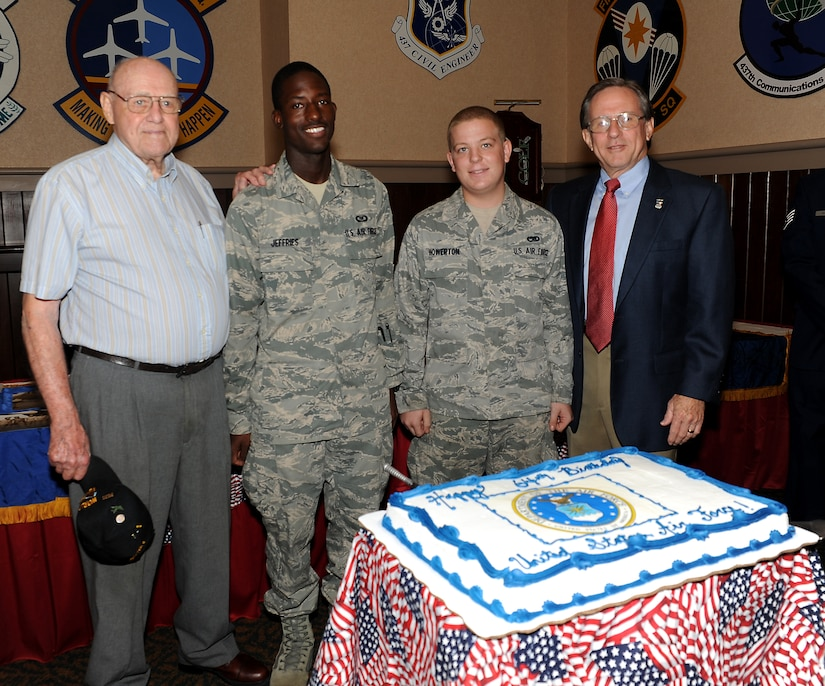 (Left to right) Robert Dunbar, Airman 1st Class Michael Jefferies, Airman 1st Class Don Howerton and Charles Jackson prepare to cut a birthday cake in honor of the Air Force's 64th birthday at the Charleston Club Sept. 16. Jefferies and Howerton were chosen to cut the cake because they are the youngest Airmen assigned to the 437th Airlift Wing. Howerton is assigned to the 437th Maintenance Squadron and Jefferies is assigned to the 437th Operation Support Squadron. Jackson and Dunbar were both prisoners of war and were also attending the POW/MIA luncheon held at the Charleston Club. (U.S. Air Force photo/Airman 1st Class Ashlee Galloway)