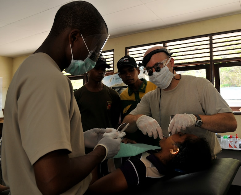 COM, Timor Leste--U.S. Air Force Staff Sgt. Richard Glass, dental assistant, prepares a 151 extraction tool for U.S. Air Force Capt. Frances Becker, dentist, for an extraction of Lanjina de Castro's left-upper molar here Sept.19. Both Glass and Becker are from Misawa Air Base, Japan. Operation Pacific Angel is a joint and combined humanitarian assistance operation led by 13th Air Force at Joint Base Pearl Harbor-Hickam, Hawaii. The operation supports U.S. Pacific Command's capacity-building efforts by partnering with other governments in the region to provide medical, dental, optometry, veterinary and engineering assistance to their citizens. (U.S. Air Force photo/Tech. Sgt. Phillip Butterfield)