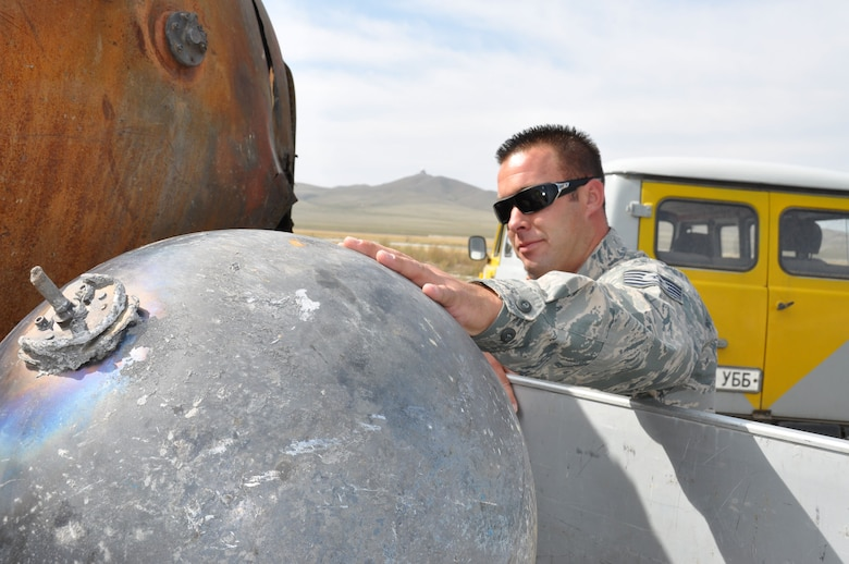 At the Chinngis Khaan International Airport, Tech. Sgt. John Lowe, 50th Aerial Port Squadron, inspects a satellite rocket's expended hydrogen tank, Aug. 26, 2011.  The tank and two other pieces of debris fell onto Mongolian soil after orbiting the Earth for nearly a decade. (U.S. Air Force photo/Master Sgt. Linda Welz)