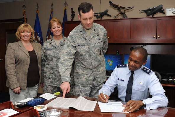 Maj. Gen. Darren McDew, Air Force District of Washington commander, signs his Combined Federal Campaign contribution form Sept. 20 on Joint Base Andrews, Md. as campaign leads (left to right) Juli Luke, AFDW protocol; Maj. Michele Holderness, 779th Medical Operations Squadron; and Lt. Col. Gregory Anderson, 11th Security Forces Squadron commander, look on. Pledges made by Federal civilian and military contributors during the campaign season support eligible non-profit organizations that provide health and human service benefits throughout the world. (U.S. Air Force photo by Staff Sgt. Christopher Ruano)
