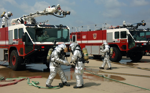Firefighters from the 375th Civil Engineer Squadron remove begin to remove their gear after an aircraft egress exercise on the flightline Aug. 3 at Scott. The gear used in this type of scenario includes Aircraft Personal Proximity Gear and a breathing apparatus. (U.S. Air Force photo/2nd Lt. Benjamin Garland)