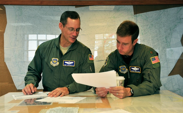 Lt. Col. Tony Caparella, 458th Airlift Squadron, and Maj. Steve Bolster, Air Mobility Command, use a map to coordinate their flight plan for the day Aug. 3 at Scott. The 458th Airlift Squadron operates 19 C-21A aircraft out of three geographically separated locations including Scott. They provide first-class Operational Airlift and Aeromedical Evacuation support both at home and while. (U.S. Air Force photo/Staff Sgt. Stephenie Wade)