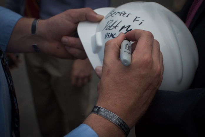 """NEW YORK --  Sgt. Dakota Meyer, the first living Marine to be awarded the Medal of Honor for actions since Vietnam, signs a construction worker's hard hat while touring the National September 11 Memorial & Museum after speaking at a ceremony, here, Sept. 21. The two black bracelets he wears are inscribed with the names of the three Marines and sailor who died in the Sept. 9, 2009 battle referenced in Meyer's Medal of Honor citation. During his speech he told the audience of mostly veterans, firefighters, police and construction workers, """"people have been calling me a hero a lot lately, but you are the real heroes... If this is what being a hero feels like, you can have it."""" For more information, visit www.dakotameyer.com. (Official Marine Corps photo by Sgt. Randall A. Clinton / RELEASED)"""