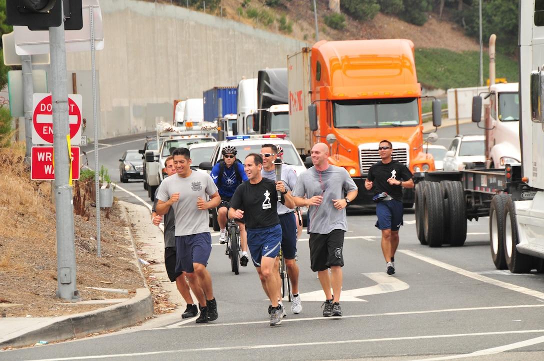 Runners are escorted across the Vincent Thomas Bridge into San Pedro. More than 50 runners representing all branches of the military services commemorated National POW/MIA Recognition Day with a 24-hour 60-plus-mile torch relay run that culminated in a wreath-laying ceremony, Sept. 16. (Photo by Lou Hernandez)