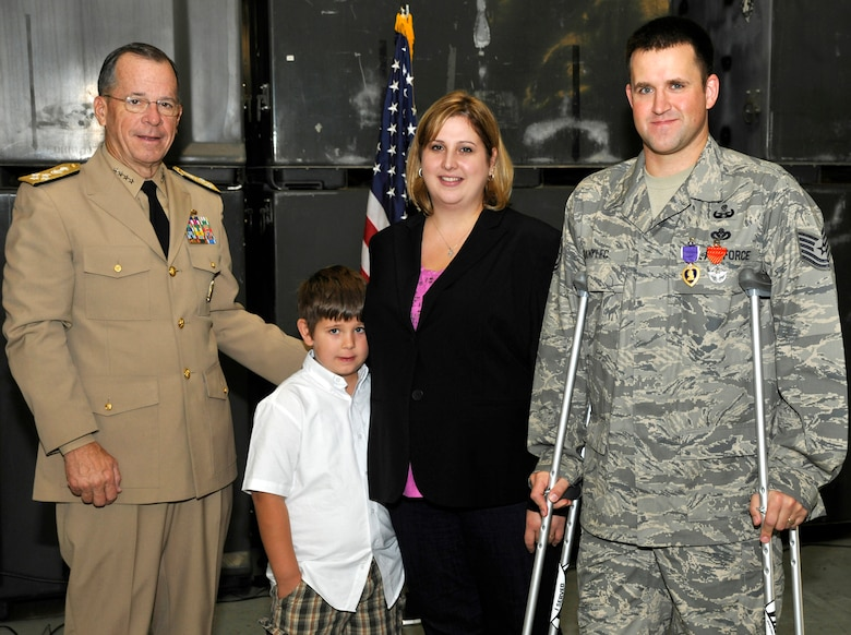 Admiral Mike Mullen, Chairman of the Joint Chiefs of Staff, stands with Tech Sgt. Michael Danylec, 11th Civil Engineer Squadron Explosive Ordnance Disposal technician, and his family after presenting Danylec with the Purple Heart on Sept. 16.  Danylec was severly injured while disarming an improvised explosive device while deployed to the Kandahar Province in Afghanistan.  (U.S. Air Force Photo/Airman 1st Class Lindsey Beadle)