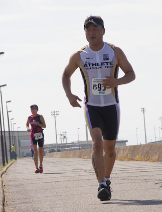 Tstuomu Morimoto, an experienced triathlon competitor, overtakes another triathlon competitor, during the Marine Corps Community Services Iwakuni Modified Triathlon here Sunday.