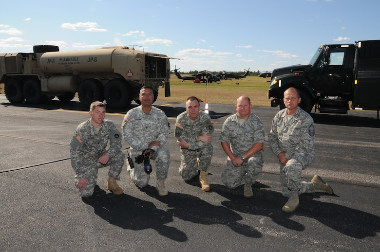 148th Fighter Wing members Senior Master Sgt. Ted Windus Jr., and Tech. Sgt. Harold Spence, pose with Army National Guard members Sgt. Nick Jefferson, Sgt. 1st Class Miguel Zamora, and Spc. Jacob Runge in front of an Army Heavy Expanded Mobility Tactical Truck (HEMTT) and an Air Force R-11 Refueler in Ely, Minn. Sept. 16, 2011.  The refueling trucks worked in tandem to keep the Blackhawk helicopters (shown in the background) in the air to dump 550 gallon loads of water on the fires in the Ely area.  (U.S. Air Force photo by Master Sgt. Ralph J. Kapustka.)