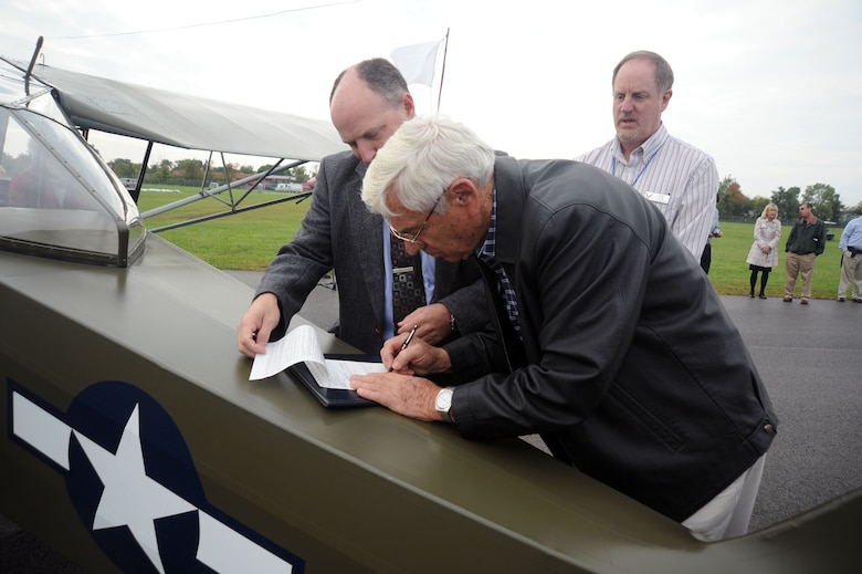 DAYTON, Ohio -- Dick Valladao signs the paperwork to donate the L-2M to the National Museum of the U.S. Air Force. Valladao piloted the aircraft, which was used at the U.S. Army Air Forces Liaison Pilot Training School during World War II, during its final flight to the museum on Sept. 28, 2011. (U.S. Air Force photo by Jeff Fisher)