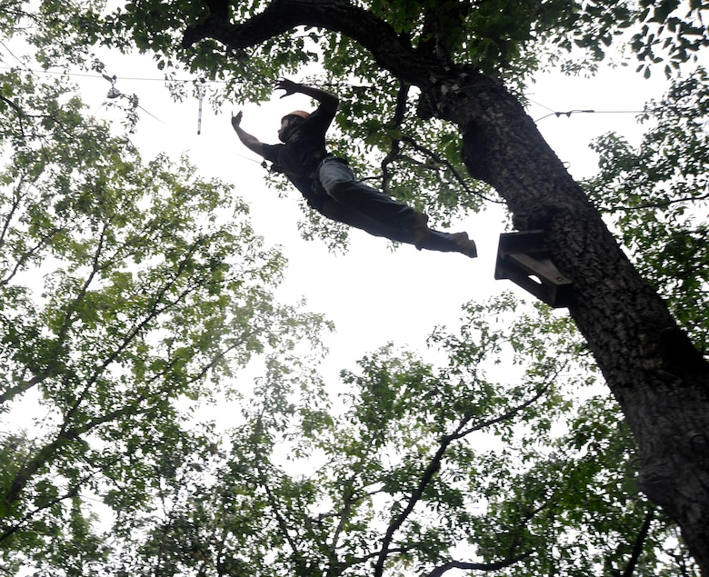 Airman 1st Class William Yano, 744th Communications Squadron cyber transport technician, without a second thought, leaps from the top of a 70-foot tree Sept. 20, to slap a pole, hanging just out of his reach. A menacing tree-climb and high-jump exercise pushed Airmen who attended the JBA Chapel Wilderness Retreat to face fears they never would have in any other capacity. (U.S. Air Force photo/Airman 1st Class Lindsey A. Beadle)