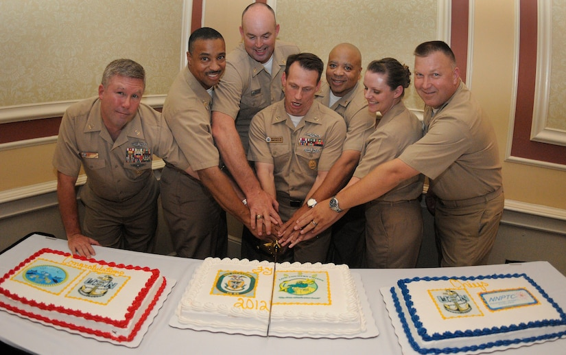 Master chief petty officers from Joint Base Charleston-Weapons Station cut a ceremonial cake with the newest, and youngest chief petty officer in attendance at the 2011 Khaki Ball, Chief Petty Officer Elizabeth Workman, who pinned on her anchors Sept. 16. The Khaki Ball, held Sept. 23, is a celebration welcoming this year's new chief petty officers into the Chief's Mess. Workman is a Machinist's Mate assigned to the Naval Nuclear Power Training Center at JB CHS - WS and has been in the Navy for six and a half years. (U.S. Navy photo/Mass Communication Specialist 1st Class Jennifer Hudson)