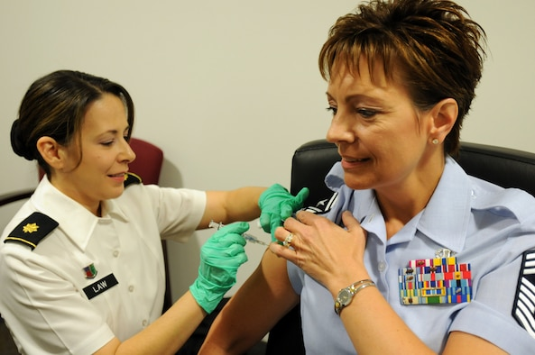 Air Force Chief Master Sgt. Denise Jelinski-Hall, the senior enlisted leader of the National Guard Bureau, receives her 2011 influenza vaccination from Army Maj. Monica Law, a nurse practitioner, at the Pentagon in Arlington, Va., Sept. 12, 2011. Jelinski-Hall said it was important for Soldiers and Airmen to keep up to date with their medical readiness, and a flu shot is an important part of mission success as the influenza season approaches. (U.S. Army photo by Sgt. Darron Salzer) (Released)