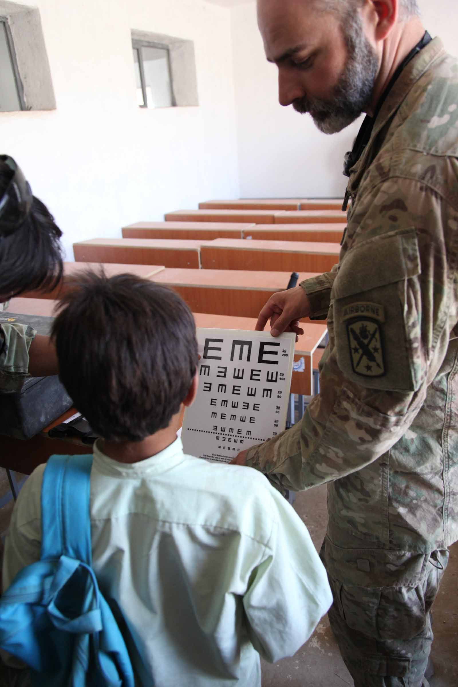 U S  Army Lt  Col  Mark Reynolds holds a visual acuity chart for an