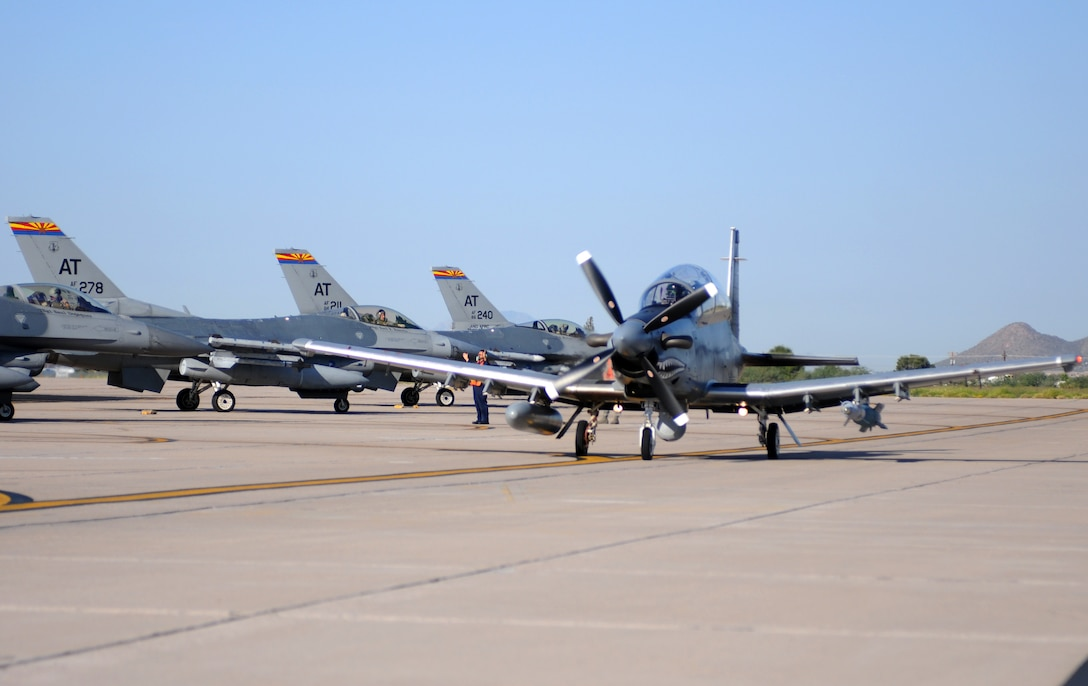 An AT-6C light attack aircraft taxis by F-16s at Tucson International Airport Sept. 28 on its way to the Barry M. Goldwater Range to drop the first precision munition ever employed on the experimental aircraft. (U.S. Air Force photo/Maj. Gabe Johnson)