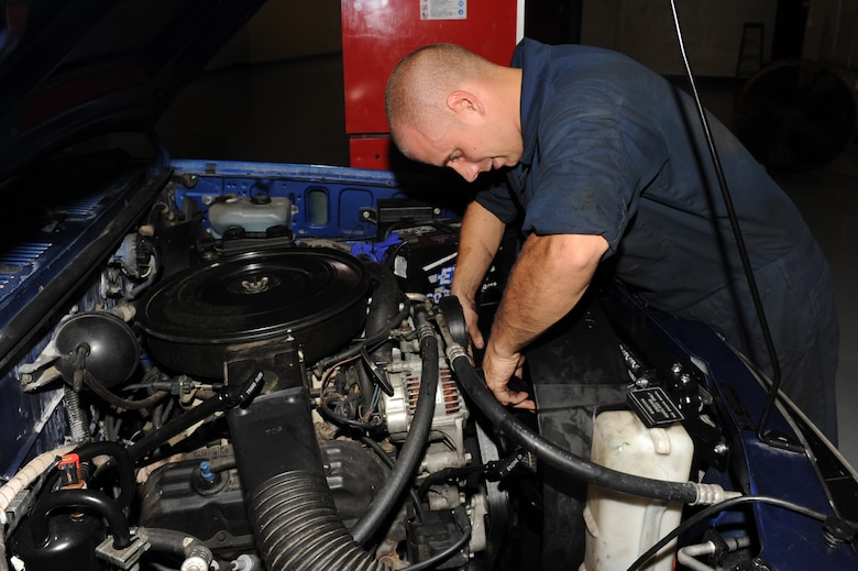 Senior Airman Brian Ball connects a vehicle fan to a stud during a maintenance repair at Seymour Johnson Air Force Base, N.C., Sept. 27, 2011. Without a fan inside of a shroud the radiator could overheat and possibly blow the motor. Ball is a 4th Logistics Readiness Squadron vehicle mechanic technician and a native of Carning, N.Y.   (U.S. Air Force photo by Senior Airman Whitney Stanfield)