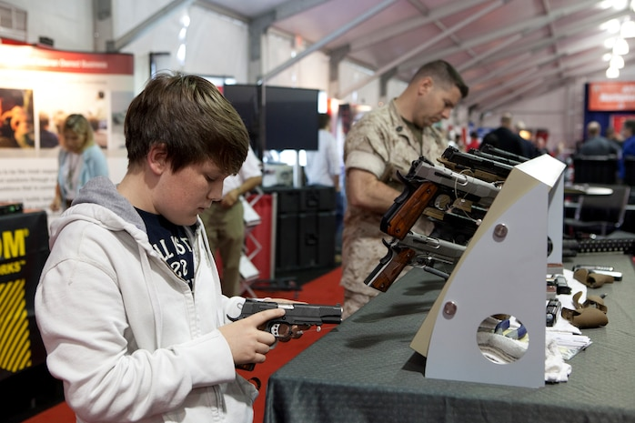 A boy inspects the latest pistol technology at a display during the Modern Day Marine Military Exposition at Marine Corps Base Quantico, Va., Sept. 29. Although many of the products were not currently in use by the Corps, the exposition gave vendors the opportunity to promote their products to Marines.