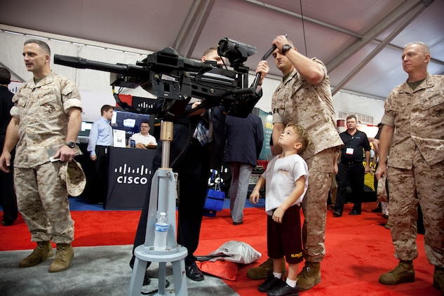 Maj. John R. Bitonti II, Headquarters and Service Battalion, helps his son try out the latest weapon technology on display during the Modern Day Marine Military Exposition at Marine Corps Base Quantico, Va., Sept. 29. Although many of the products were not currently in use by the Corps, the exposition gave vendors the opportunity to promote their products to Marines.
