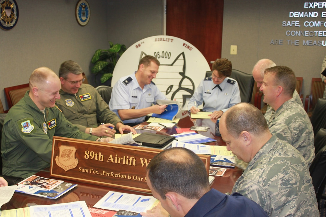 Col. Jacqueline D. Van Ovost 89th Airlift Wing commander, and Col. Dale S. Holland, 89th Airlift Wing vice commander, along with wing senior Leaders, sign pledge forms for the 89th Airlift Wing's Combined Federal Campaign kickoff ceremony Sept 28.