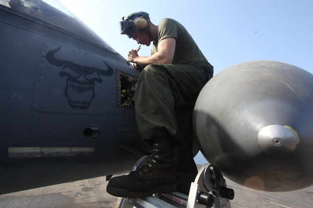 Lance Cpl. Darynn Chartier, a native of Glendale, Ariz., and air frames mechanic with the airframes section for Marine Medium Tiltrotor Squadron 261 (Reinforced), 24th Marine Expeditionary Unit, conducts routine maintenance on an AV-8B Harrier aboard the USS Iwo Jima (LHD 7), Sept 29. The aviation maintenance crews work around the clock to ensure the 24th MEU's aircraft are always ready to fly in support of the various missions they could be called for.