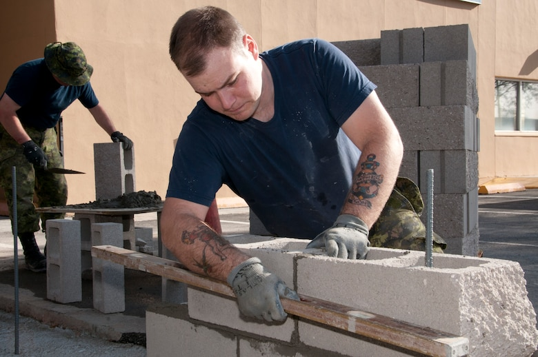 Royal Canadian Air Force Cpl. Judd Bettle, right, and Pvt. Robert Yates construct a patio wall in front of the 162nd Fighter Wing dining facility March 26. (U.S. Air Force photo/Tech. Sgt. Hollie Hansen)