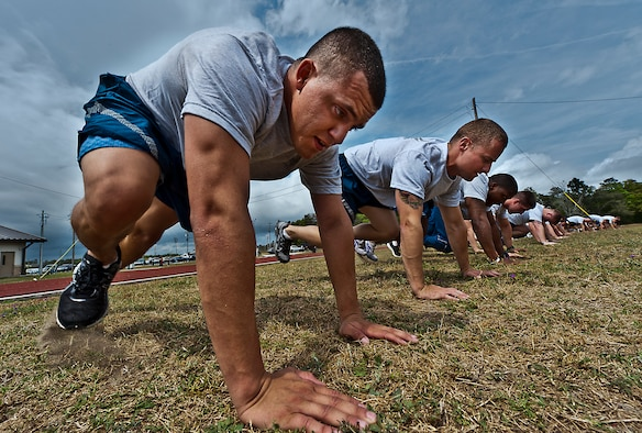 "Staff Sgt. Bobby Brewer, of the 46th Maintenance Group, and more than 20 other Airmen perform ""mountain climbers"" during a physical training leader class March 30 at Eglin Air Force Base, Fla.  PTLs lead their flights and squadrons in group PT sessions during the week throughout the base.  (U.S. Air Force photo/Samuel King Jr.)"