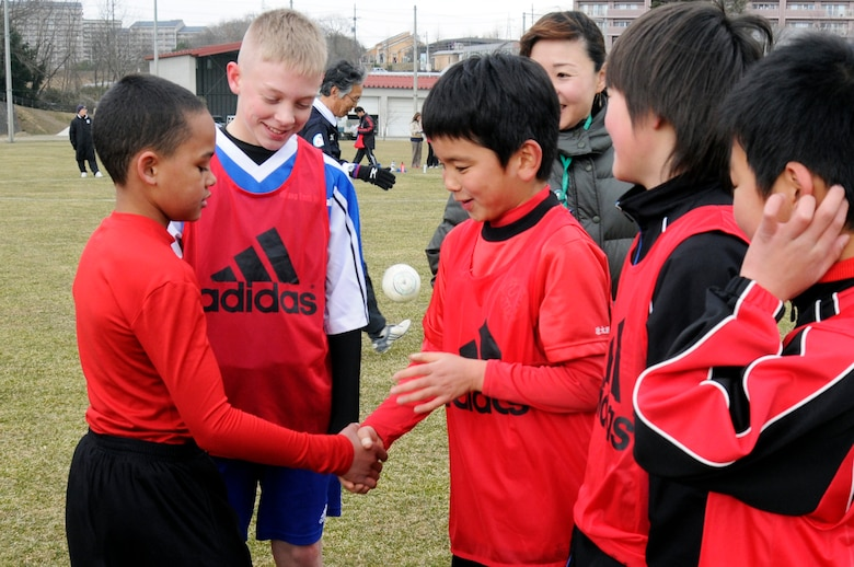The son of U.S. Air Force Capt. Jennifer Franks, 35th Medical Surgical Squadron, shakes hands with a Japanese child from Sendai on his team during a Japan-U.S. soccer exchange at Sendai, Japan, April 1, 2012. After playing against each other, the children from Misawa Air Base and Sendai city were put into mixed teams where they formed friendships through their love for soccer. (U.S. Air Force photo by 2nd Lt. Son Lee/Released)