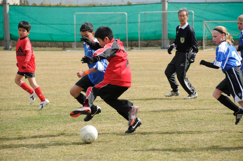 Children from the city of Sendai and Misawa Air Base race to grab a soccer ball during a joint-youth soccer match at Sendai, Japan, April 1, 2012. The children from Misawa Air Base played against the children of Sendai during the first half of the game, and then during the second half of the game, the children were put into mixed teams to encourage joint interaction. (U.S. Air Force photo by 2nd Lt. Son Lee/Released)
