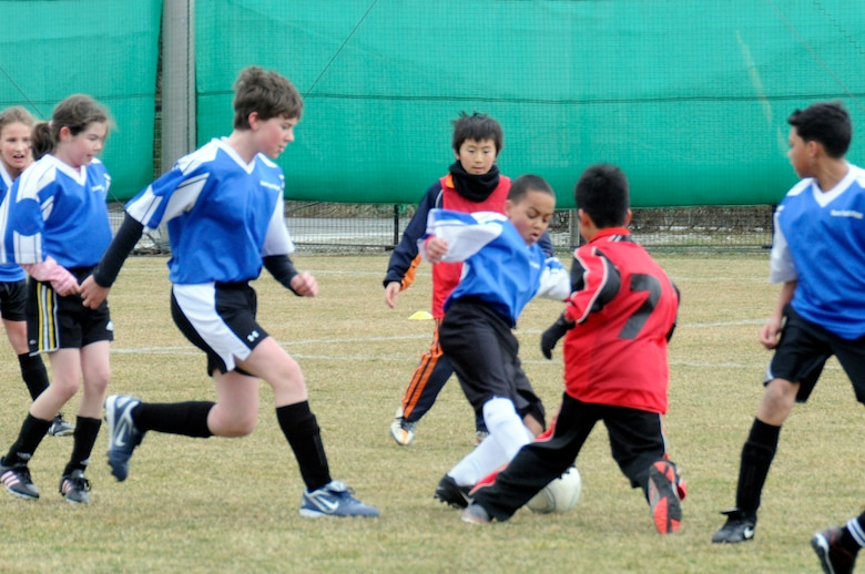 The son of U.S. Air Force Capt. Jennifer Franks, center, 35th Medical Surgical Squadron, goes in to steal the ball during a joint-youth soccer game at Sendai, Japan, April 1, 2012. The City of Sendai extended an invitation for American elementary school students from Misawa Air Base to participate in a Japan-U.S. soccer exchange before a professional match between the U.S. Major League Soccer women's team and Japanese women's team later that night. (U.S. Air Force photo by 2nd Lt. Son Lee/Released)