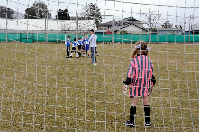 The daughter of U.S. Air Force Capt. Justin Kandle, 35th Medical Surgical Squadron, plays goalie during a warm-up activity before a joint-youth soccer game at Sendai, Japan, April 1, 2012. To celebrate the 100-year anniversary of the Japanese gift of more than 3,000 cherry trees to the United States, the city of Sendai invited 14 children from Misawa Air Base to play in a soccer match before Hope Solo and the rest of the U.S. Major League Soccer women's team played the Japanese women's national team later that night. (U.S. Air Force photo by 2nd Lt. Son Lee/Released)