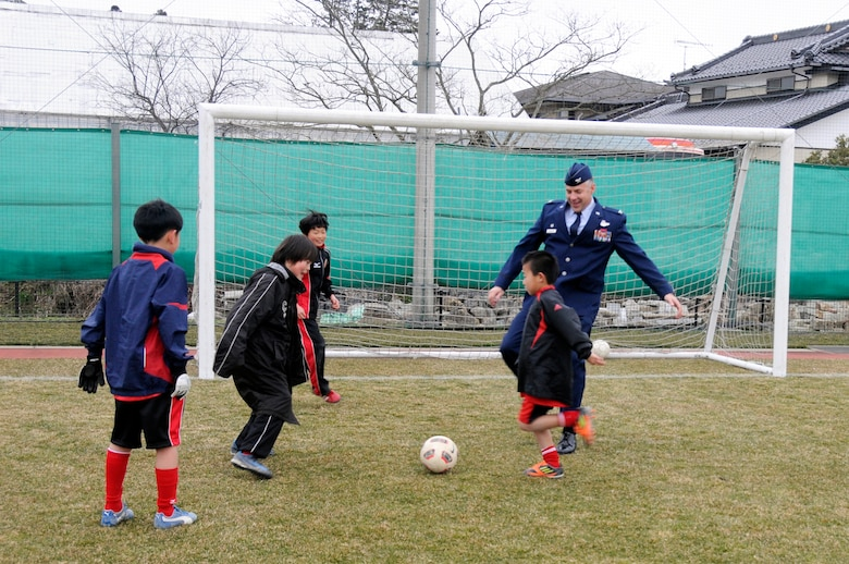 U.S. Air Force Col. Sam Shaneyfelt, 35th Operations Group commander, warms up with Japanese children before a game at Sendai, Japan, April 1, 2012. Fourteen children from Misawa Air Base were invited to play in a joint-youth soccer game against Japanese children from Sendai to commemorate the centennial of the Japanese gift of more than 3,000 cherry trees to the United States in 1912. (U.S. Air Force photo by 2nd Lt. Son Lee/Released)