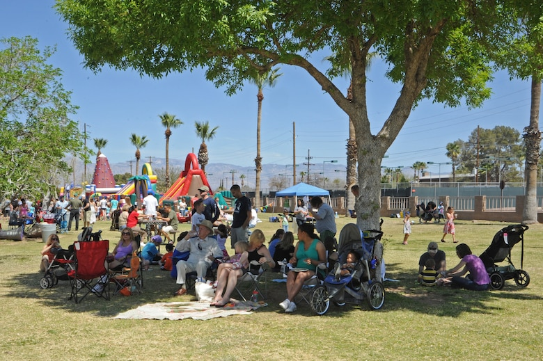 Attendees of the D-M 50 picnic sit in the shade while they eat at Davis-Monthan Air Force Base, Ariz., March 31, 2012. This picnic is held annually to show appreciation to the men and women of the 355th Fighter Wing and its tenant units. (U.S. Air Force photo by Airman 1st Class Camilla Griffin/Released)