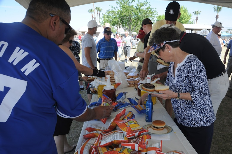 Attendees of the D-M 50 picnic prepare their plates at Davis-Monthan Air Force Base, Ariz., March 31, 2012. All D-M Airmen and their families were invited to enjoy free food and various activities, including a car show, K-9 demonstration and a petting zoo. (U.S. Air Force photo by Airman 1st Class Camilla Griffin/Released)