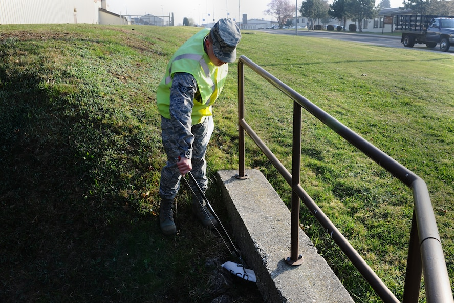 SPANGDAHLEM AIR BASE, Germany – Airman 1st Class Nicholas Chapman, 52nd Equipment Maintenance Squadron aircraft armament apprentice, picks up a piece of paper during his morning Eifel Pride trash route near Arnold Boulevard here April 3. Eifel Pride is a mandatory two-week program for first-term Airmen stationed here immediately following initial technical training school. The program helps Airmen become oriented to the base, allows them to finish their in-processing and aids in the ongoing 52nd Fighter Wing goal of becoming United States Air Forces in Europe's most environmentally-friendly wing. (U.S. Air Force photo by Airman 1st Class Dillon Davis/Released)