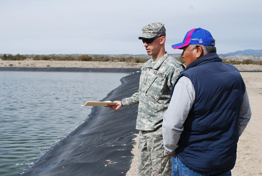 COCHITI PUEBLO, N.M., -- Officer in Charge of FEST Maj. Seth Wacker gathers information from Pete Trujillo about the drainage and sanitation of Pueblo de Cochiti's sewage lagoon system.