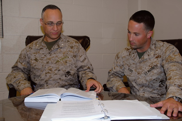Lt. Col. Alex Ray, left, Staff Judge Advocate, and Capt. Tyler Gludt, deputy staff judge advocate, MCLB Albany, review regulations concerning ethics rules regarding gifts to Marines and requests for support.