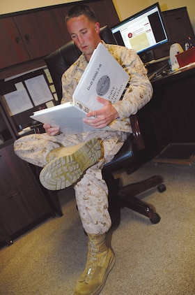 Capt. Tyler Gludt, deputy staff judge advocate, Marine Corps Logistics Base Albany, reads the Joint Ethics Regulations governing community support requests.
