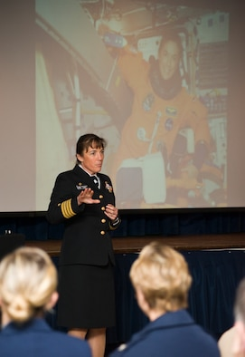 Navy Capt. Heidemarie Stefanyshyn-Piper, Naval Surface Warfare Center Caderock Division commander, addresses a Joint Base Andrews audience during an Andrews Leadership Series event at the Community Activity Center on March 29.  The background photo depicts Capt. Stefanyshyn-Piper serving as an astronaut during the space shuttle Endeavor mission in 2008.  (Photo/Bobby Jones)