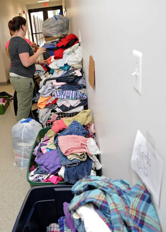 Volunteers sort through piles of clothes March 30 that were donated to the Andrews Attic in support of families effected by a base housing fire. (U.S. Air Force photo/Senior Airman Laura Turner)