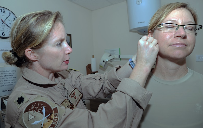SOUTHWEST ASIA - Lt. Col. (Dr.) Darlene Smallman applies acupuncture needles to Maj. Amber Hirsch's ear April 4, 2012. Hirsch suffers from hip pain and has found acupuncture the only treatment that helps her. Smallman, a flight surgeon deployed to the 380th Air Expeditionary Wing from the Pentagon, studied at the Air Force Acupuncture Center on Joint Base Andrews, Md. Hirsch is the wing judge advocate. (U.S. Air Force photo/Staff Sgt. J.G. Buzanowski)
